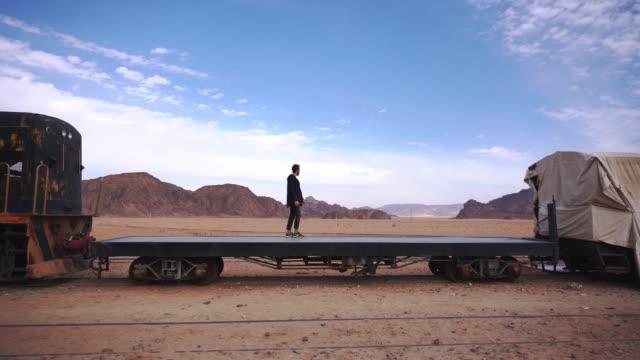 vidéos et rushes de homme debout sur la plate-forme du train dans le désert de wadi rum - wagon