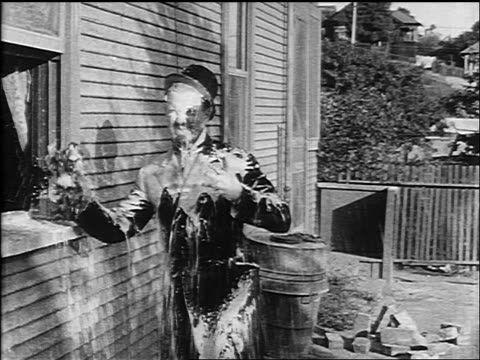 b/w 1913 man (ford sterling) standing outside of window being hit by milk being thrown out - 1913 stock-videos und b-roll-filmmaterial
