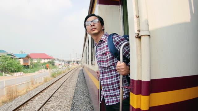 4K : Man standing side by side of train