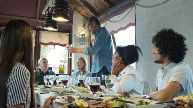 アルゼンチンのパリラレストランで多世代の集まりで父親に乾杯を提案するために立っている男 - アルゼンチン点の映像素材/bロール