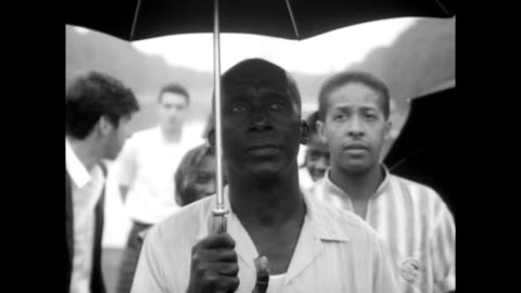 vidéos et rushes de man standing under umbrella in the rain on the washington mall / preparations for security are made, man holding walkie talkie / african american... - 1963