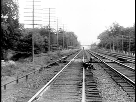 1910 b&w man standing up and walking on railroad tracks after being thrown off train/ usa - railway track stock videos & royalty-free footage