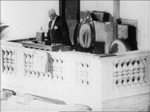B/W 1929 man standing up at desk to ring bell at New York Stock Exchange / newsreel