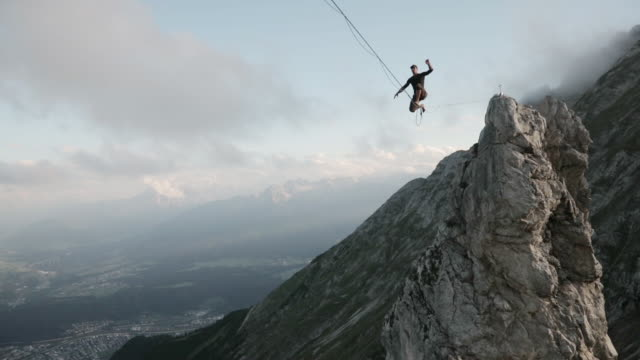 man standing up on a highline in the alps