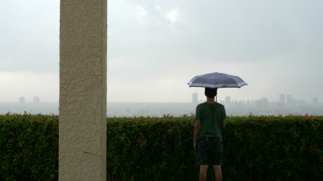man standing with an umbrella on the rooftop - one mid adult man only stock videos & royalty-free footage