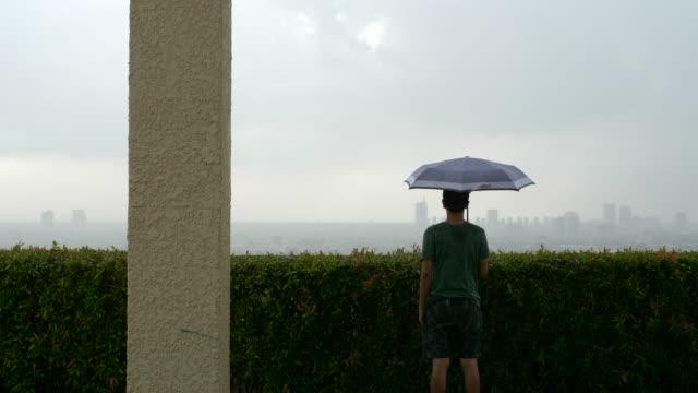 stockvideo's en b-roll-footage met mens die zich met een paraplu op het dak bevindt - alleen mid volwassen mannen