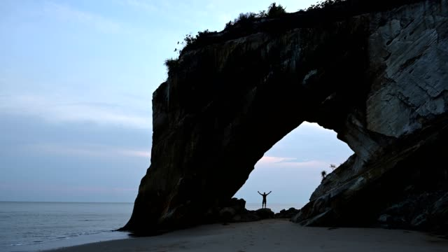 アーチの下に腕を伸ばして立っている男 - サラワク州点の映像素材/bロール