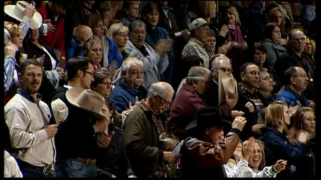 stockvideo's en b-roll-footage met man standing with hat on chest as american national anthem sang and crowd at all american quarter horse championships applauding sot woman riding... - quarter