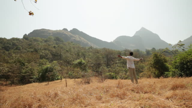 man standing with his arms outstretched in the forest - braccio umano video stock e b–roll