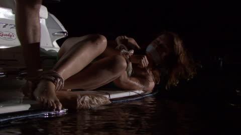 vídeos de stock, filmes e b-roll de a man stands above a woman's body bound with rope. - atado
