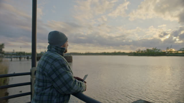 man stands and looks out pensively over the cape fear river at sunset. - only men stock videos & royalty-free footage