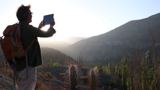 Man stands at desert overlook, takes pic with digital tablet