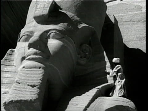 man stands atop a giant statue of ramses ii in abu simel, egypt. - history stock videos & royalty-free footage