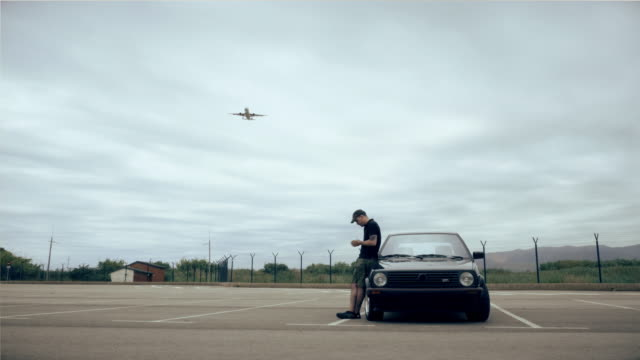 Man stands behind his car looking at the smartphone while a aeroplane lands