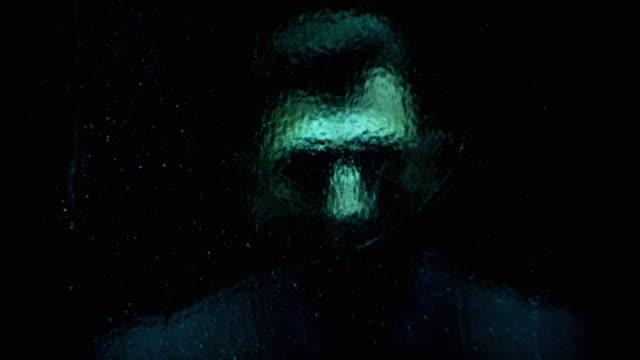 vídeos de stock, filmes e b-roll de a man stands behind textured glass. - surreal