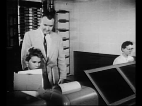man stands behind woman seated at machine and they look at a document / side view woman types, probably on a teletype machine, as she looks at... - man and machine stock videos & royalty-free footage