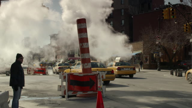 A man stands by a steam pipe waiting to cross the street on 7th Ave South in New York city