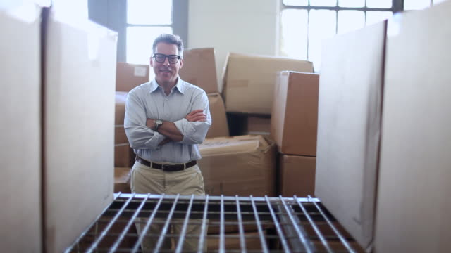 """MS Man stands crossing his arms in front of empty space on shelf full of boxes / Brooklyn, New York, United States"""