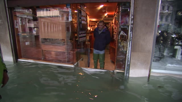 vídeos y material grabado en eventos de stock de man stands in flood water and talks with a shop owner at st. mark's square in venice, italy. - environment or natural disaster or climate change or earthquake or hurricane or extreme weather or oil spill or volcano or tornado or flooding