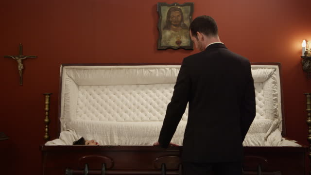 vidéos et rushes de a man stands in front of a coffin cursing the god that took his wife - cercueil