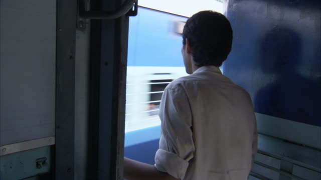 a man stands in the doorway of a moving train in india. - doorway stock videos & royalty-free footage