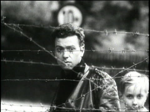 a man stands morosely behind a barbed wire fence during the building of the berlin wall in germany - 1961 stock-videos und b-roll-filmmaterial