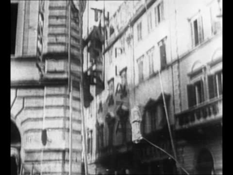 Man stands on ladder at front of building hits stone emblem on EXT with hammer / pan emblem guided by ropes falls to street narrowly missing a...