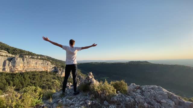 vidéos et rushes de l'homme se tient sur le dessus de montagne, enlève le masque et ouvre des bras dans la pose de liberté - la vingtaine
