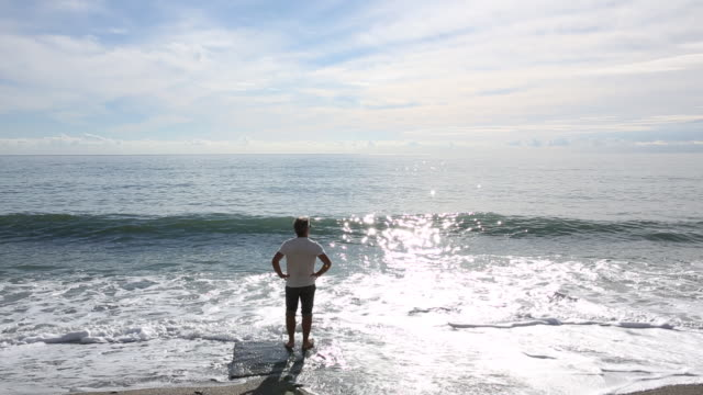 Man stands on pedestal at water edge, watches sea surf