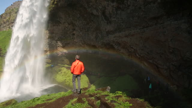Man stands on rock looking at tall waterfall in Iceland
