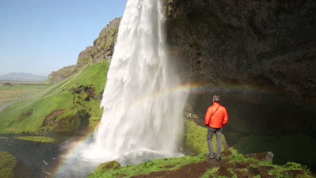 man stands on rock looking at tall waterfall in iceland - falling water stock videos & royalty-free footage
