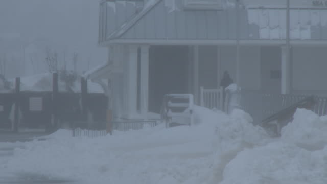 A man stands on the balcony of his home along the Jersey Shore as strong winds and heavy snow create whiteout conditions during the historic Blizzard...