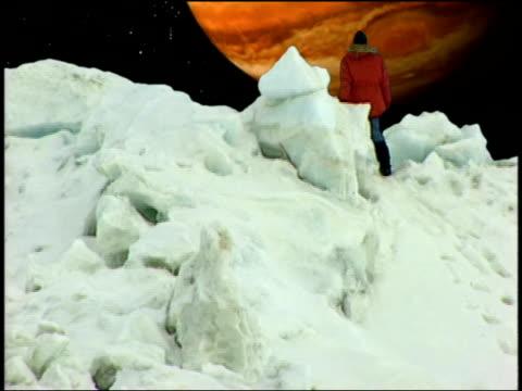 vídeos de stock e filmes b-roll de a man stands on the snowy surface of europa and looks at jupiter. - júpiter