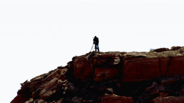 a man stands on top of a cliff in the utah desert with a tripod and video camera. - zoom out stock videos & royalty-free footage