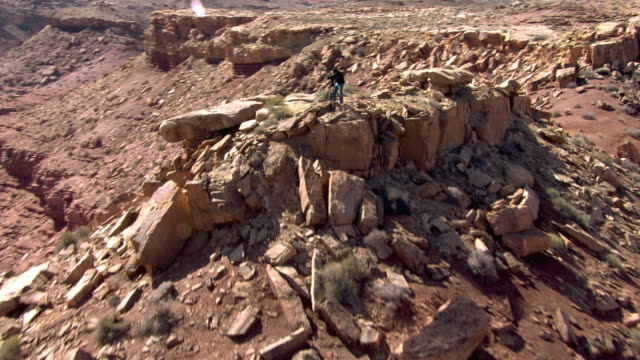 vidéos et rushes de a man stands on top of a cliff in the utah desert with a tripod and video camera. - lac powell
