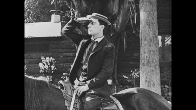 1921 man (buster keaton) stands on top of a horse, falls off, and has trouble getting back on - horse stock videos & royalty-free footage