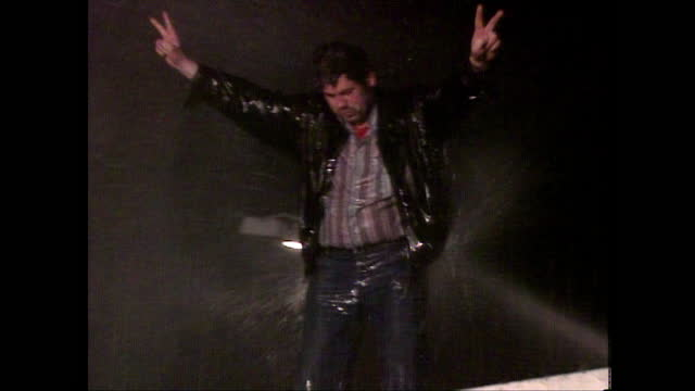man stands on top of the berlin wall celebrating while being sprayed with a water cannon; 1989. - 1989 stock videos & royalty-free footage