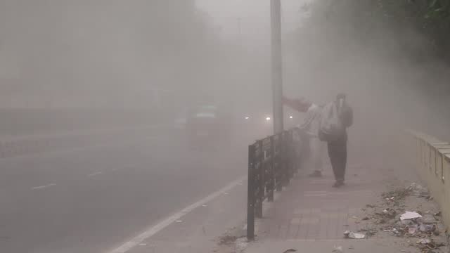 man stands outside as a commuter walks by during a dust storm on may 01, 2021 in guwahati, india. - surface level stock videos & royalty-free footage