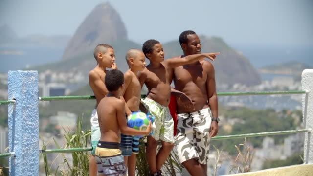 vídeos de stock e filmes b-roll de man stands with kids overlooking rio de janeiro - família com quatro filhos