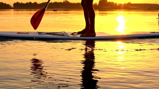 slo mo man stand-up paddleboarding - using a paddle stock videos & royalty-free footage