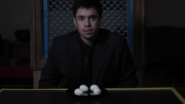 man staring at camera and then boiled eggs on a black plate in a dark dining room - 全套西裝 個影片檔及 b 捲影像