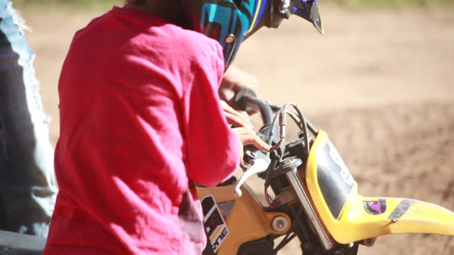 vidéos et rushes de a man starting dirt bike for young boy on a sunny summer day. - kelly mason videos