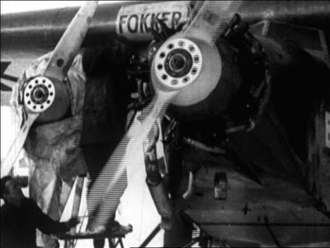 man starting propeller of airplane for byrd's flight over the north pole / newsreel - 1926年点の映像素材/bロール
