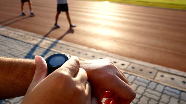 man starts jogging in running track - wrist stock videos & royalty-free footage
