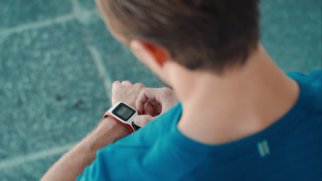 l'uomo inizia il jogging in ambiente urbano - smartwatch video stock e b–roll