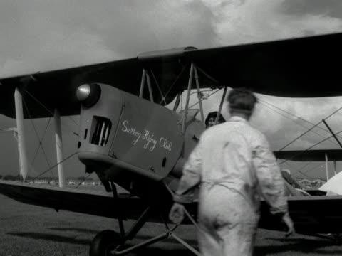 stockvideo's en b-roll-footage met a man starts the propeller of a tiger moth plane at croydon airport - start en landingsbaan