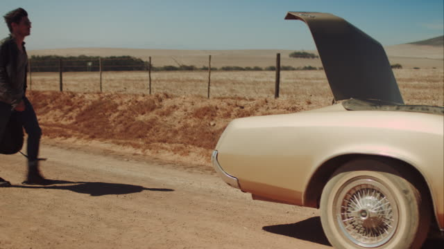 Man starts trip with retro car on dirt road