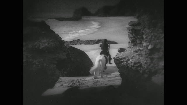 man (douglas fairbanks) steals a horse and rides along the shoreline at night - anno 1926 video stock e b–roll