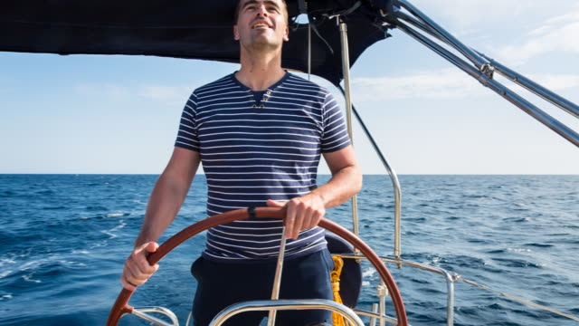 cu man steering modern sailing yacht in mediterranean sea - guidance stock videos & royalty-free footage