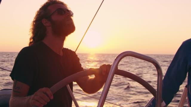 4K Man steering sailboat on tranquil, sunny sunset ocean, slow motion